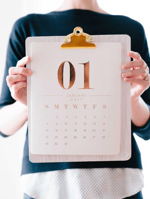 Vrouw houd een kalender op klembord vast