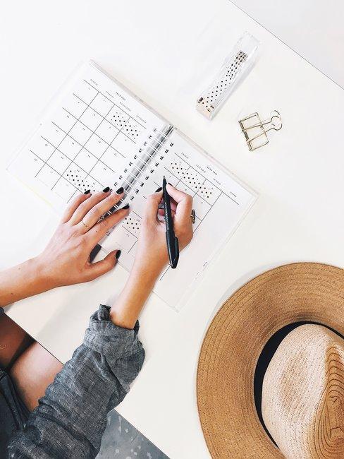 Witte tafel van boven gefotografeerd met checklist die wordt afgewerkt en hoed trouwkaarten