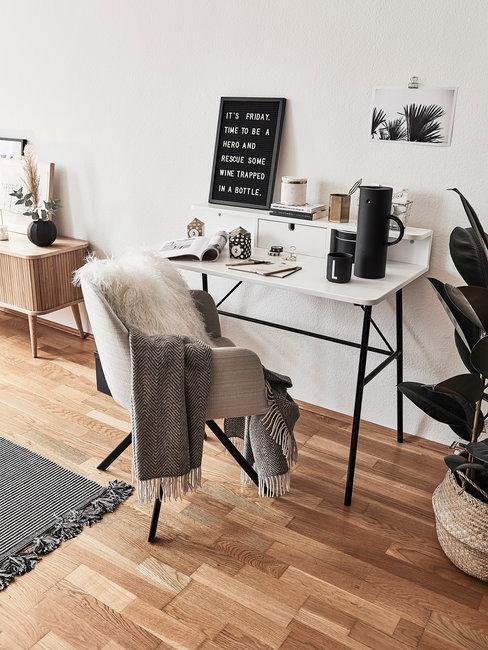 Houten vloer met wit bureau en bureaustoel in grijs met zwarte assecoires