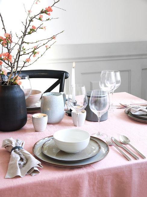 Halve tafel met roze tafekleed en tafelsetting in natuurlijke tinten met witte muur