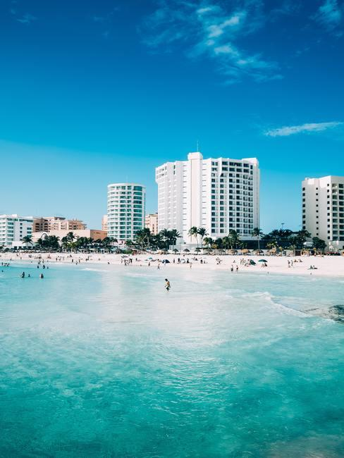 Hotels aan een wit zandstrand met blauwe zee en lucht