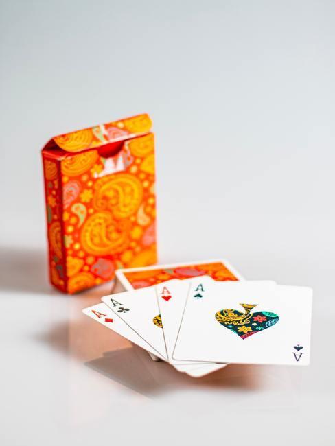 Kaartspel in oranje doosje op witte achtergrond