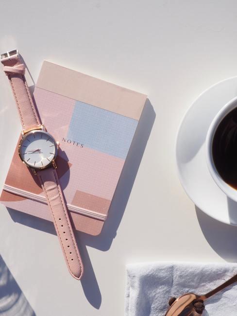 Witte tafel met roze notiteboekje en roze horloge met kopje koffie