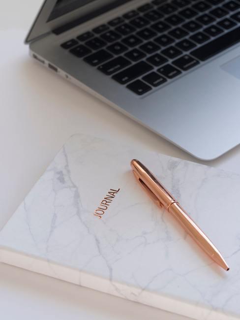 Witte tafel met marmeren dagboek en macbook op achtergrond