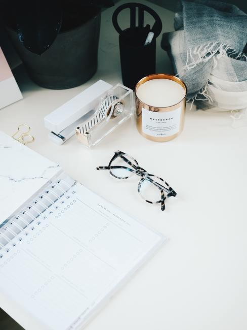 Witte tafel met ringband notitieblok bril plakband en kaars in gouden pot