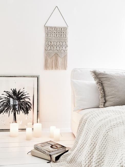 Slaapkamer in bohemian style interieur met wit linnen en witte muren met wanddecoratie