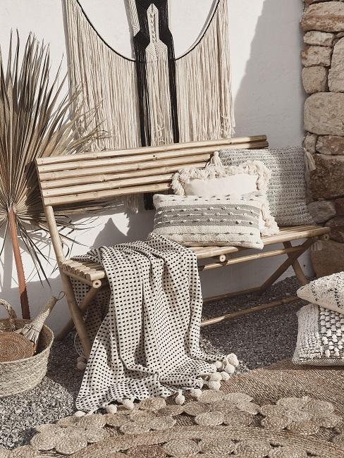 Kleine tuin in boho style met bamboe bankje en accessoires in aardetinten