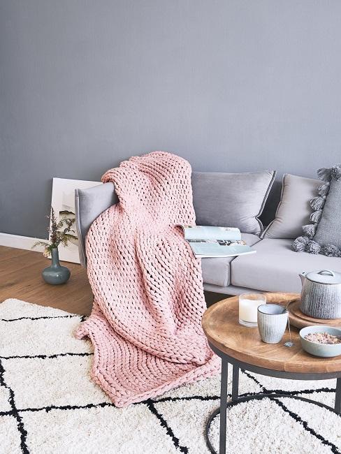 Bekleding reinigen: oud roze deken voor grijze muur met grijze bank