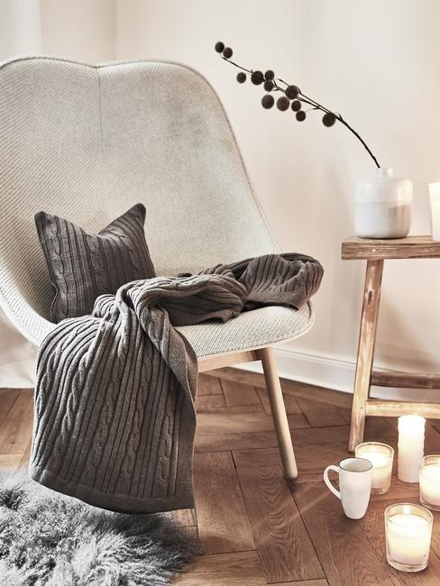Grijze fauteuil op houten visgraatvloer met kaarsen