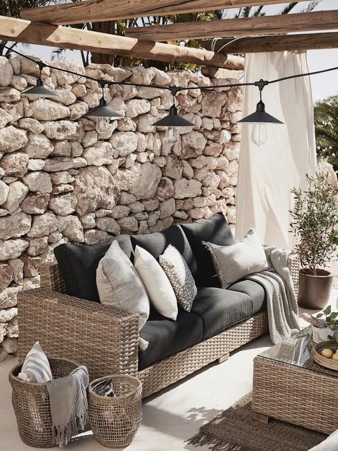 Originele mediteraanse stenen muur met weens vlechtwerk outdoor meubels
