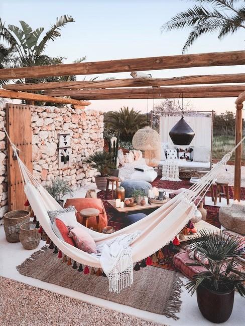 Houten pergola met hangmat en loungeset voor stenen muur