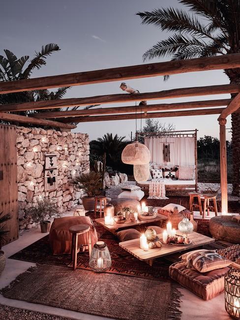 Houten pergola in de avond met kaarsen en decoratie op houten tuinmeubels