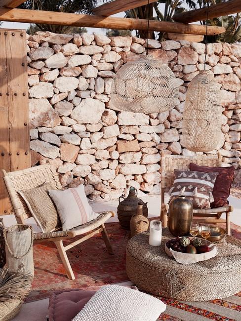 Stenen muur met bohemian rotan gevlochten meubels