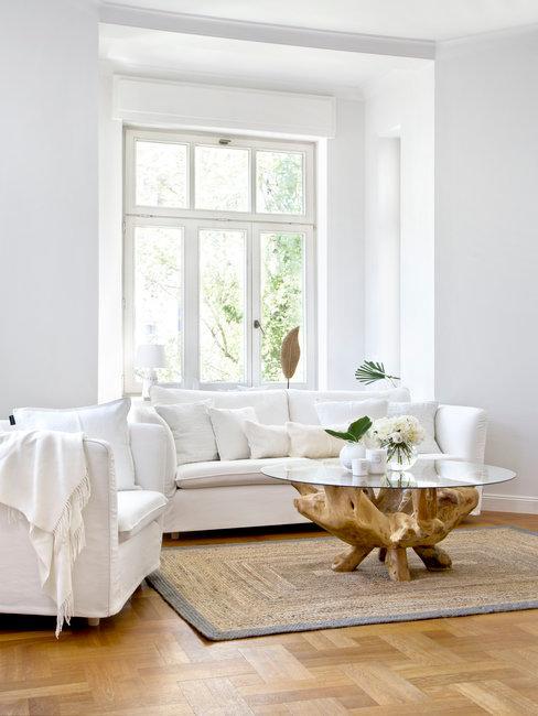 Witte woonkamer met witte zitbanken, houten vloer met rieten vloerkleed en salontafel van hout en glas