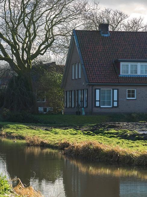 landelijk huis met rivier ervoor