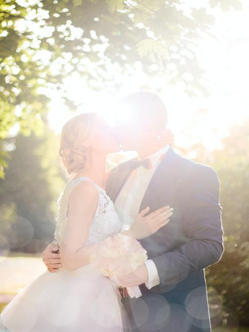 Kussend bruidspaar in de zonneschijn bij een huwelijk in bohostijl