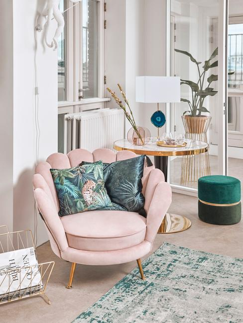 Roze loungestoel met gouden details in woonkamer met sitetable van marmer met groene poef