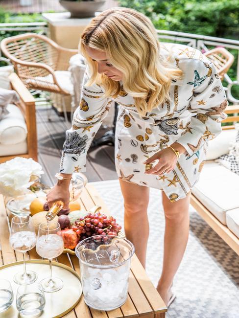 Delia schenkt champagne in glazen op het terras