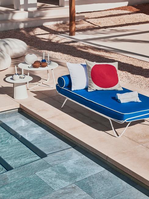 Een blauwe ligstoel met kussens naas het zwembad