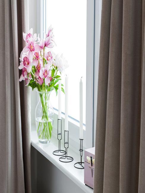raam met ervoor glazen vaas met roze bloemen en witte kaarsen en grijs-bruine gordijnen