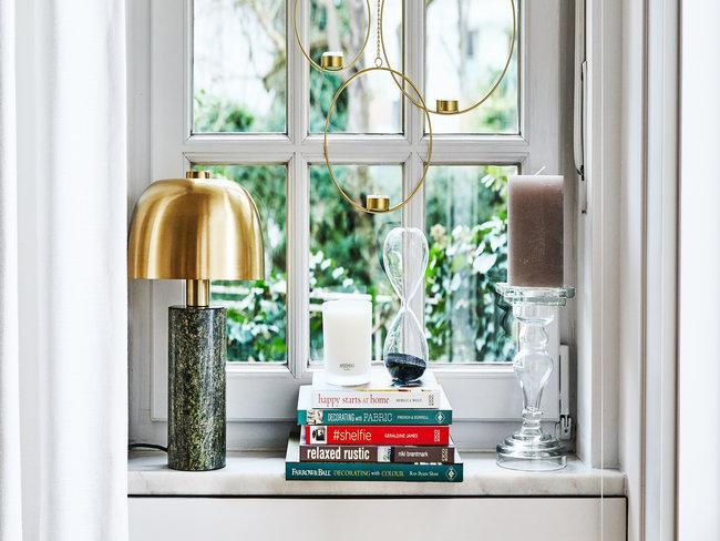 Lamp, kaars, boeken en andere decoratieve objecten op raamkozijn met grijze gordijnen