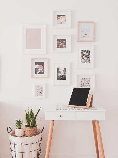 Wanddecoratie van fotolijsten en witte sidetable naast een kruk met plantenpotten