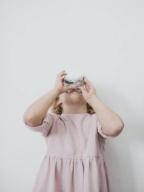 Kind in roze jurk met grijze achtergrond