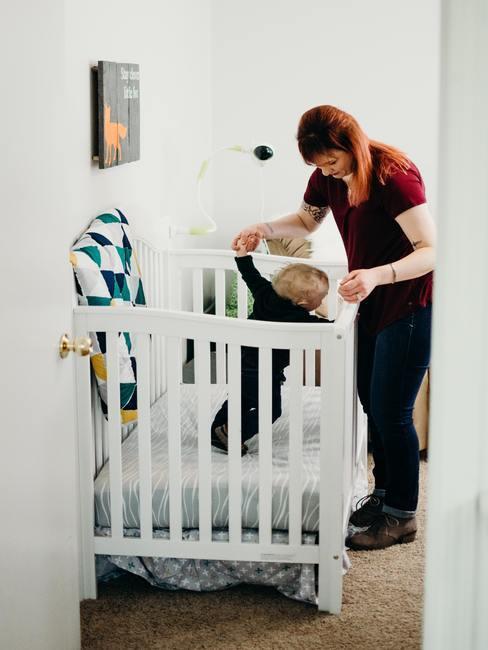 Moder met baby in wit babybedje met groene en okergele details babykamer okergeel