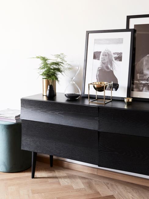 Zwarte sideboard met ingeliste print en goudkleurige vaas met bloemen