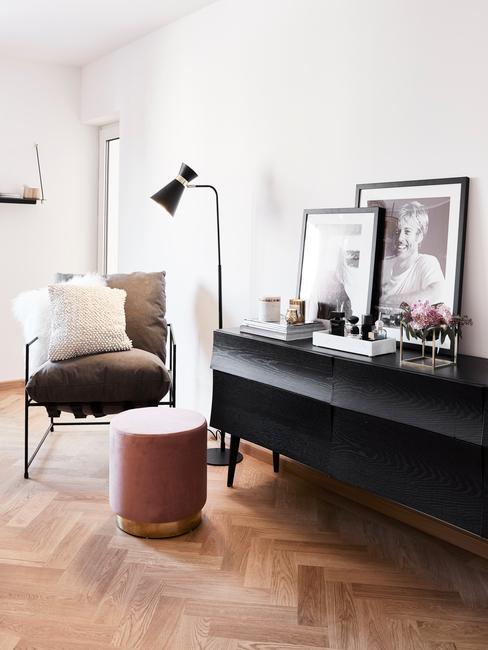 Zwarte sideboard van donker hout met ingeliste print en decoraties naas een fluwelen poef en fauteuil