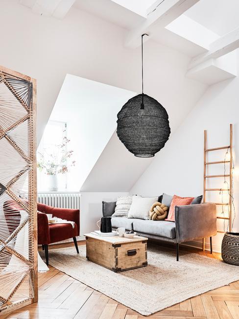 Grijze zitbank met sierkussens naast een houten salontafel en zwarte hanglamp