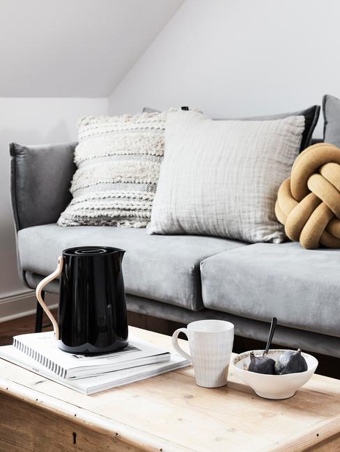 Velvet: grijze zitbank met sierkussens naast een houten salontafel met koffietafelboeken en zwarte kan en witte mok