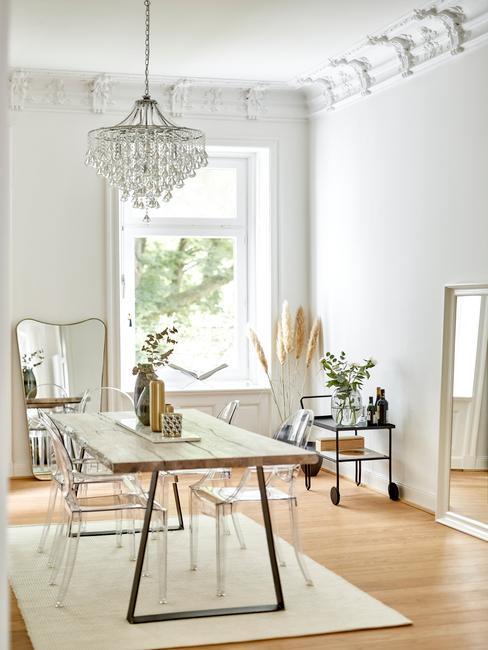 Jadalnia w stylu glam z drewnianym stołem, krzesłami z plexi i dekoracjami