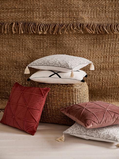 Rattanowy puf obok którego i na którym znajdują się poduszki dekoracyjne w różnych kolorach