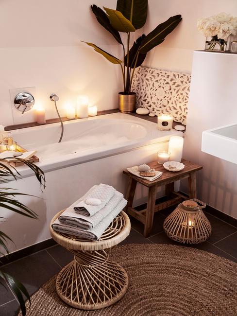 Łazianka z wanną, stoliczkiem z ręcznikami i sizalowym dywanem oraz dekoracjami