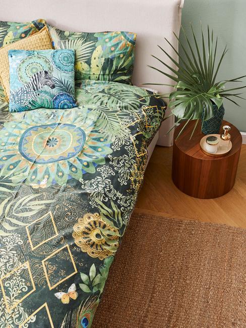 Zbliżenie na łóżko z kolorową narzutą oraz rośliną w doniczce