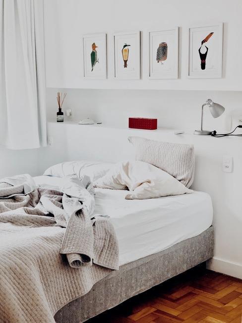 Biała sypialnia w sloku z pojedynczym łożkiem oraz dekoracjami na ścianie