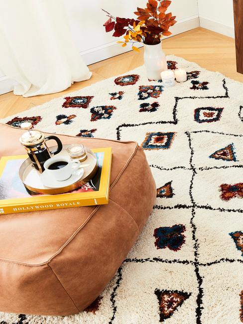 Zbliżenie na wzorzysty, biały dywan oraz na skórzany, kwadratowy puf