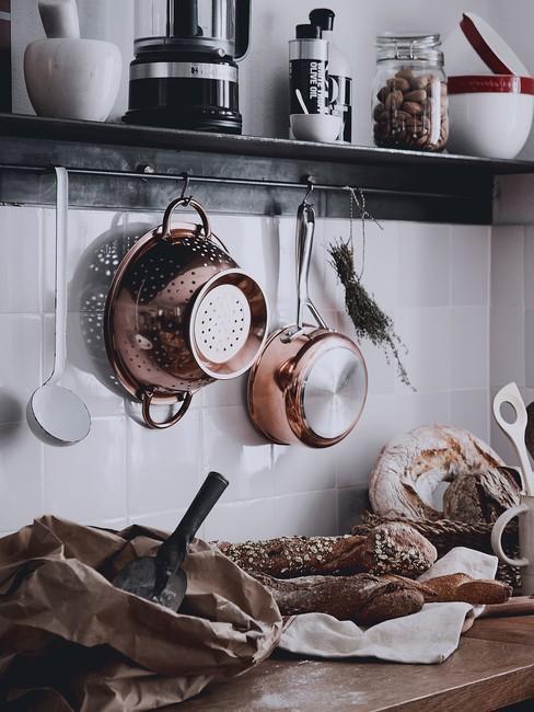 Kuchnia z białą ścianą, czarnymi meblami oraz półką ścianną z organizerem kuchennym