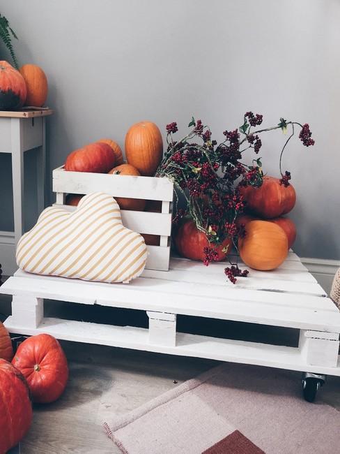 Biała ławka zrobiona z euro palety z dekoracjami na jesień