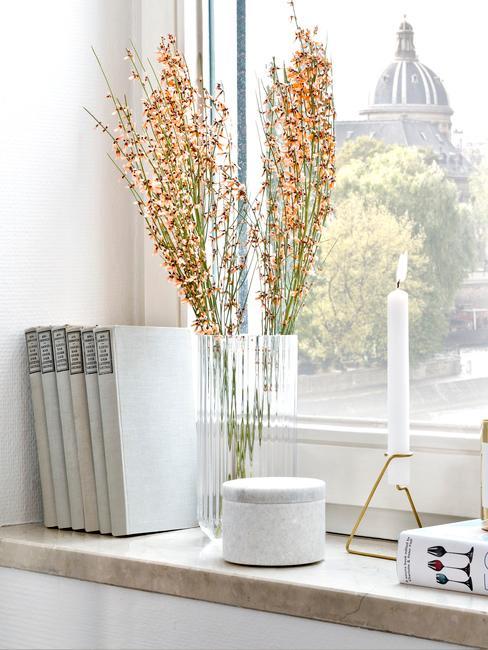 Parapet z kwiatami, świeczką oraz książkami