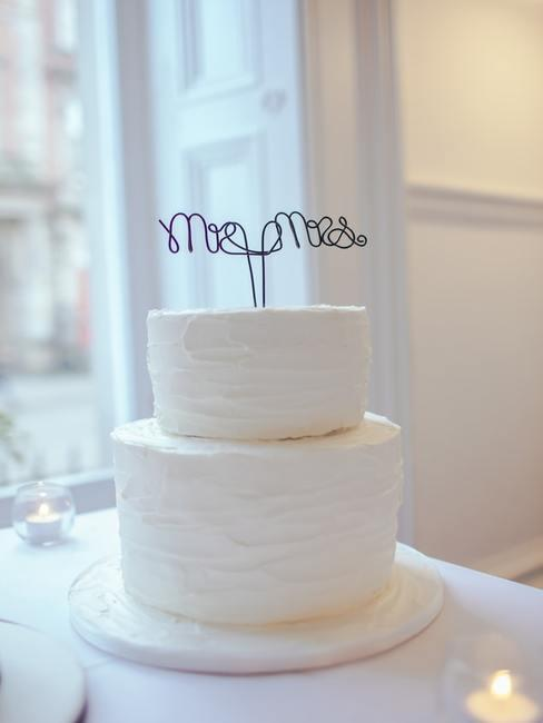 Minimalistyczny tort weselny z białym lukrem oraz dekoracją