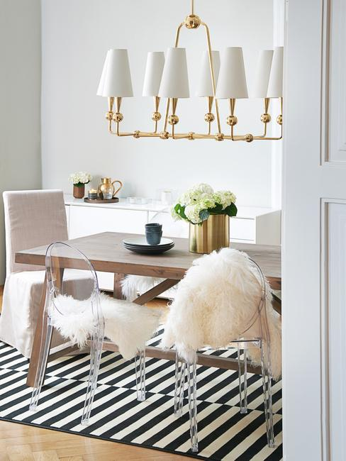 Jadalnia z drewnianym stołem, dywanem oraz żyrandolem