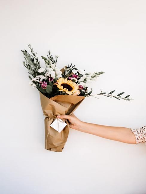 Dziewczyna trzymająca w ręku bukiet kwiatów owinięty w papier
