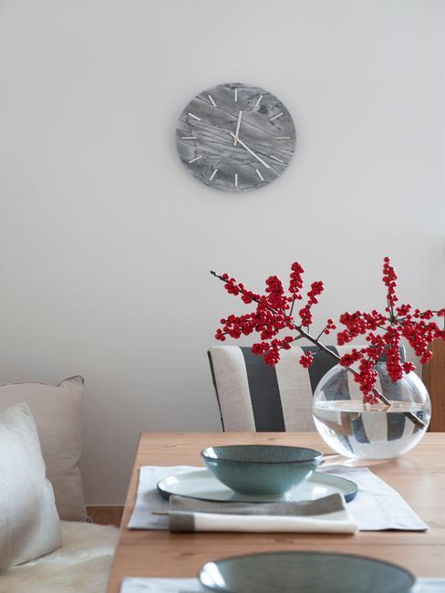 Jadalnia z zastaionym stołem i szarym zegarem na ścianie