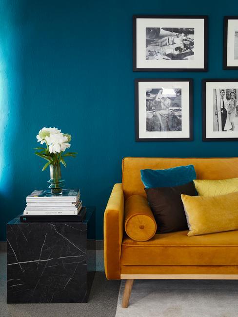 Fragment turkusowego salonu z sofą w kolorze ochry
