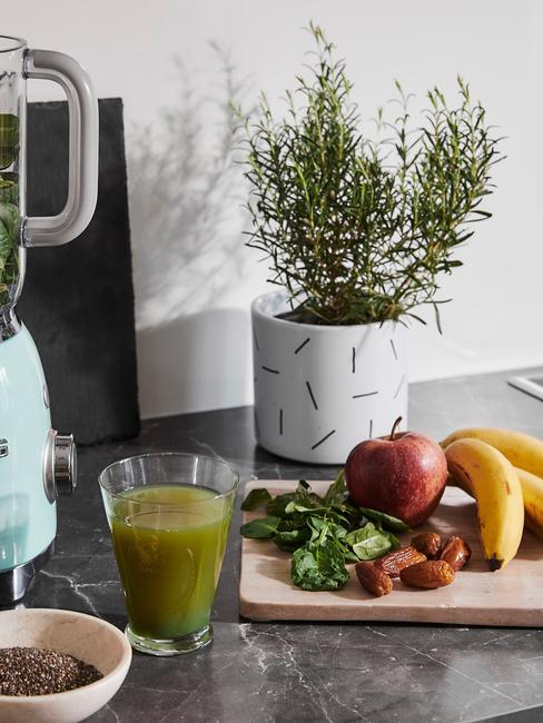 Szklanka z zielonym sokiem stojąca obok drewnianej deski z owocami oraz oregano w doniczce