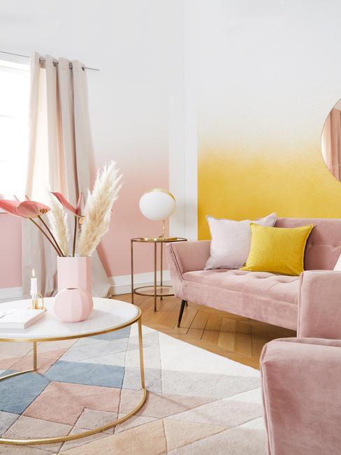 Żółto - różowy salon z sofa, białym stolikiem kawowym oraz dekoracjami
