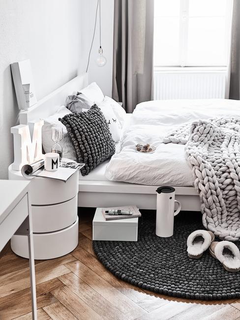 Biała sypialnia w stylu skandynawskim z czarnym, okrągłym dywanem