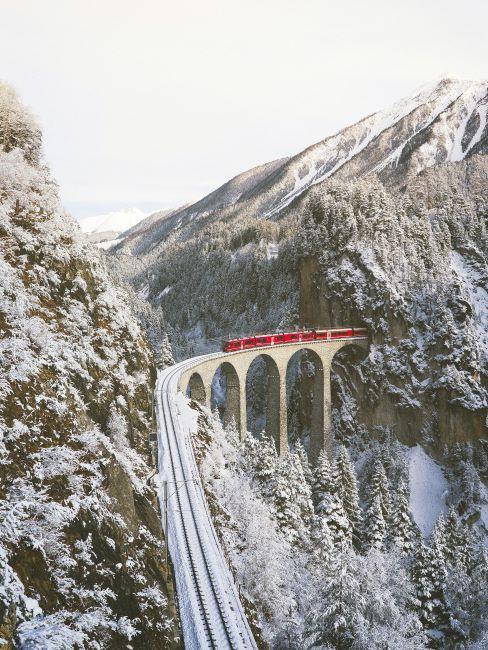 Czerwony pociąg przejeżdzający przez przełęcz pomiędzy górami